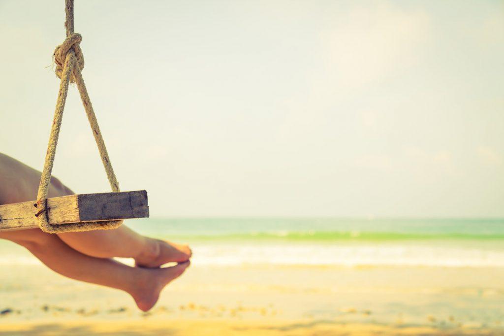 Vrouw schommel op strand
